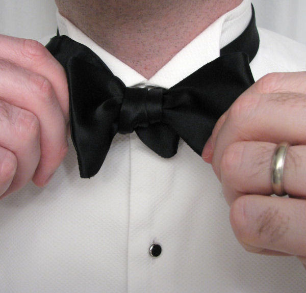 Black tie guide style tying a bow tie once the longer end is pushed far enough through that it can be released it without falling back out it will form a folded wing simultaneously pull it ccuart Images